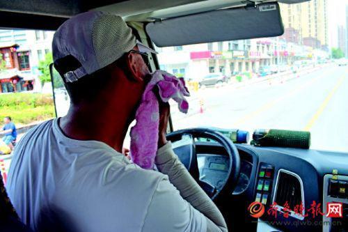 车里很闷热,陈师傅用毛巾擦汗。齐鲁晚报·齐鲁壹点记者 刘飞跃 摄