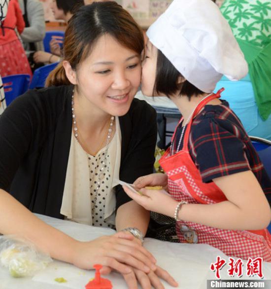 ↑资料图:一位母亲正在接受六岁的女儿献上深情一吻。中新社发 刘可耕 摄