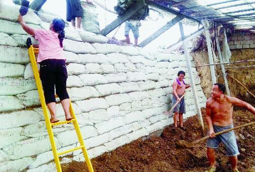 村民们帮助纪仁海修复西红柿大棚。