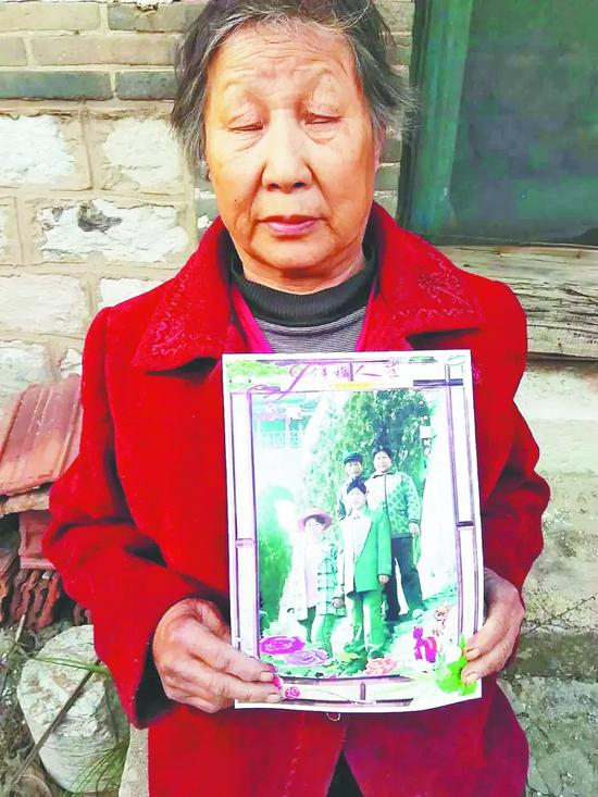 在老宅里,岳女士的母亲拿着一家四口人的合影。