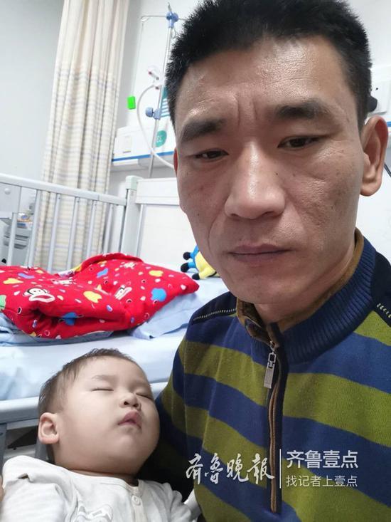 唐一轩躺在爸爸唐绍龙的怀里睡着了。