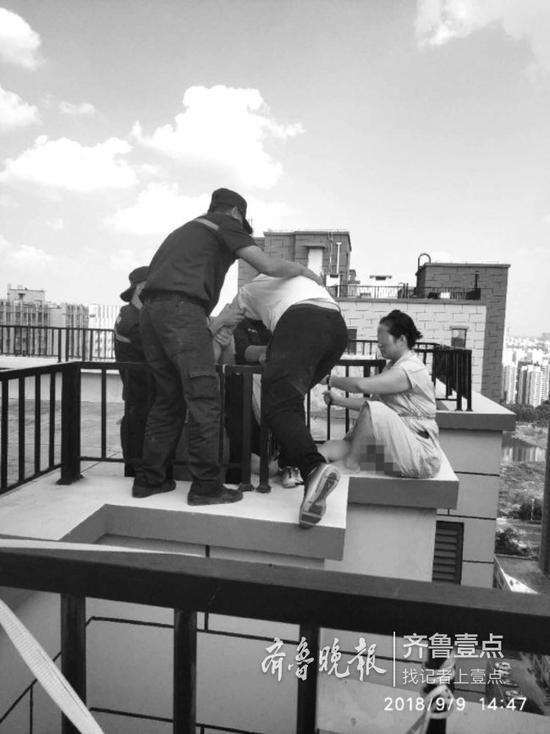 """花御馨苑小区的四名保安闻讯赶到楼顶天台,将该男孩""""拖""""了回来。 侯昌伟 摄"""