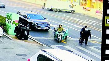 24日,监控拍下崔凯扶老人过马路的暖心一幕。