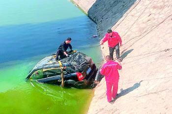 ▲救援人员正在营救坠河车辆。