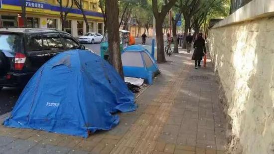 垃圾桶旁边搭起两顶帐篷
