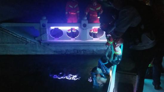 众人合力对落水女子施救。片/消防供图