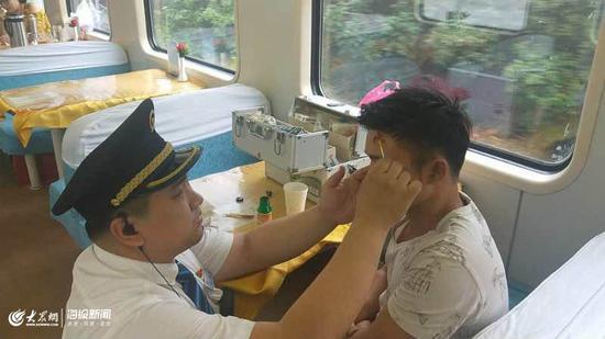 K205次列车长曹峻明为小伙清理伤口
