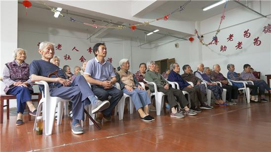 陆丁兴为敬老院老人们放映电影(一排,左二)。图片来源:苏州文明网