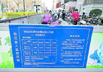 停车场围栏上悬挂着收费标准公示牌。