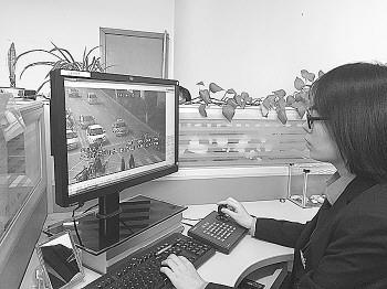 工作人员正在操作监控探头,对路口嫌疑车辆进行搜索。记者 吴永功 摄