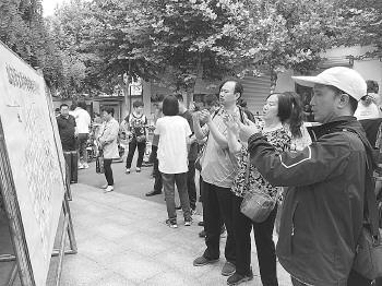 山师附中考点外,众多家长用手机拍摄考场安排。记者 郭春雨 摄