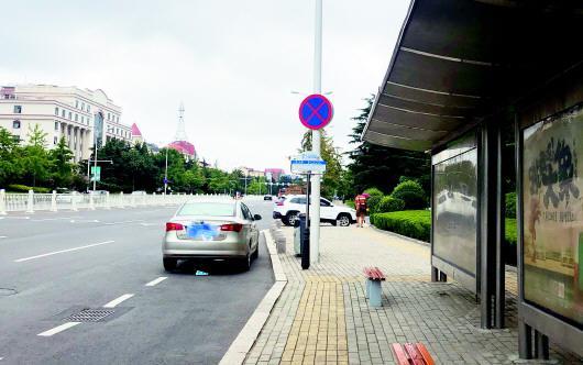 恩马文景园车站内,一辆小轿车无视禁停标志占据公交港湾停车。