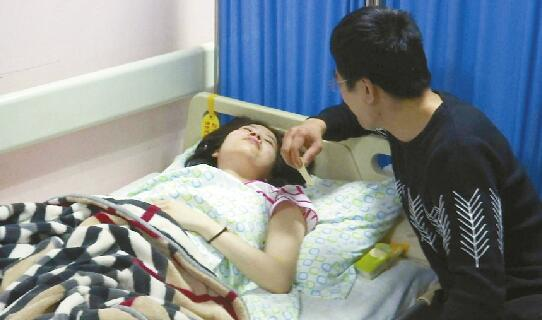 唐先生在病床旁照顾妻子 记者俞丹 摄