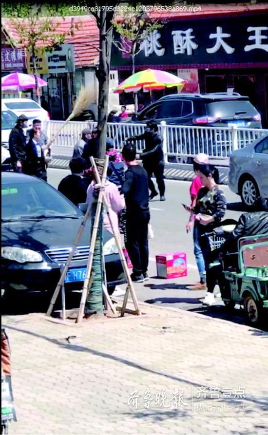 持刀劫匪被协警一扫帚撂倒,最终在警民合力之下被制服。视频截图