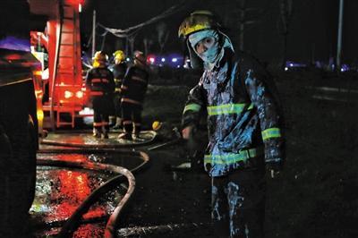 3月22日,在前线参加灭火救援的消防员拍打掉身上的泡沫。