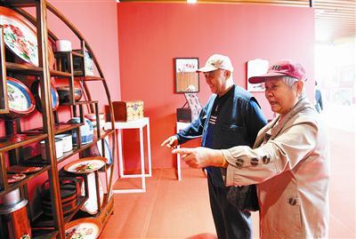 ▲一对老人在欣赏老物件展览。刘栋 摄