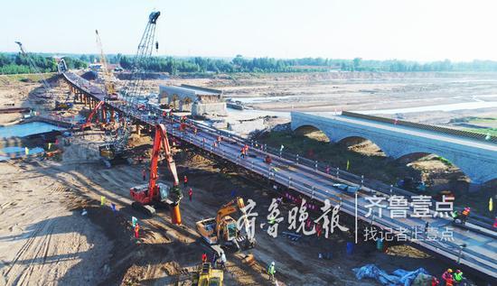 8日,大桥建设现场,一侧是被洪水冲毁的原桥梁。
