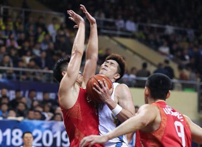 3月20日,江苏苏州肯帝亚队球员吴冠希(中)在比赛中拼抢。新华社发
