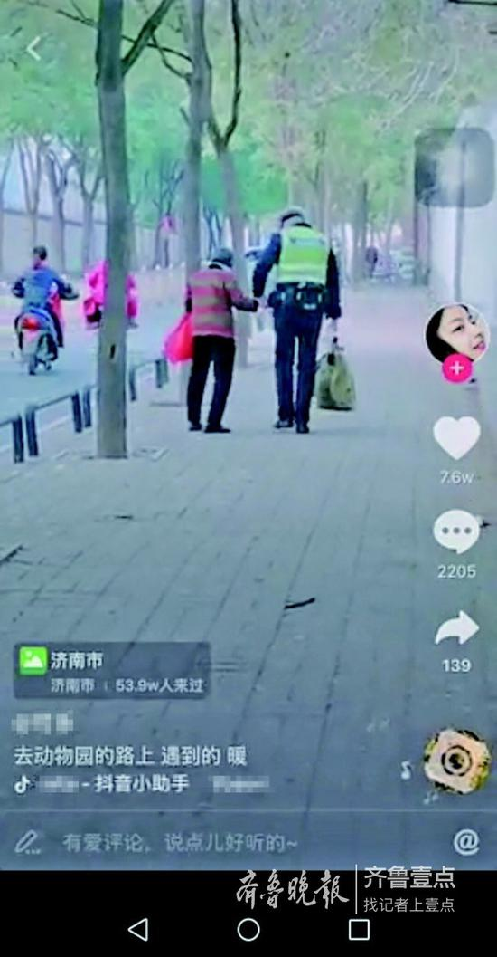 交警小哥哥一手拎着大包,一手暖心地牵着老奶奶。 视频截图