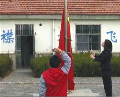 竹岔岛小学,每周一,教师薛倩倩都会和9岁读二年级的学生薛文炫,一起升旗。