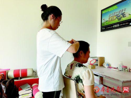 周晓明正在给母亲扎辫子。