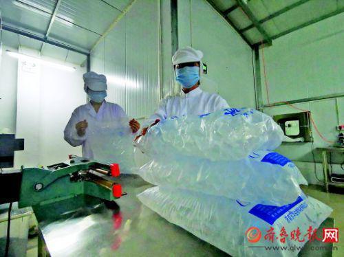 工作人员正在将密封后的冰块放在一起,准备运往冰库。
