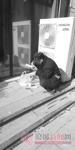 农民工蹲在寒风中吃盒饭。