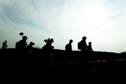 烈日下,志愿者们携带笨重的设备,走在寻访下一位老党员的山路上。
