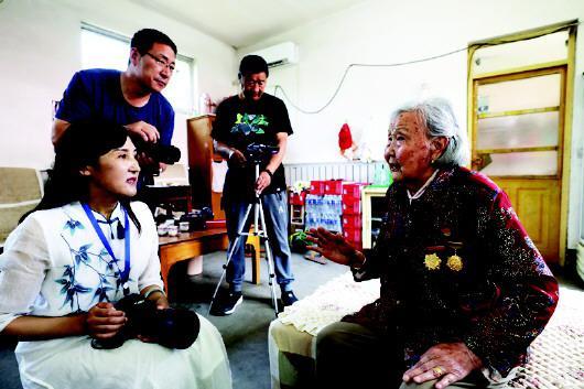 志愿者正在采访拍摄95岁的老党员徐沛荣,徐沛荣家住沂南县界湖街道。