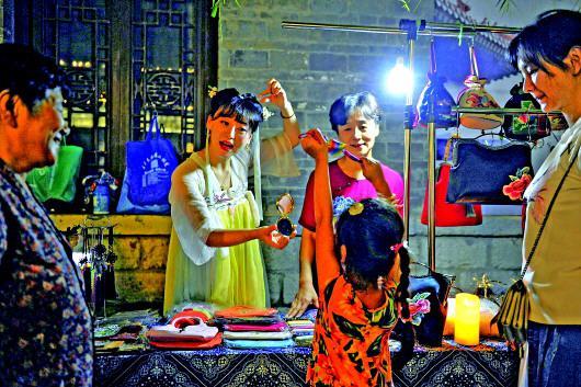 百花洲夜市上,张慧母女正在和喜爱手工制作的市民交流。