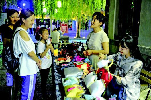 张慧母女正在百花洲夜市上向市民介绍手工制作的方法。