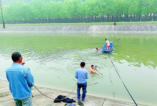 救援现场,赤膊的潜水员正将钩子固定在水下的轿车上,而落水司机此时早已获救