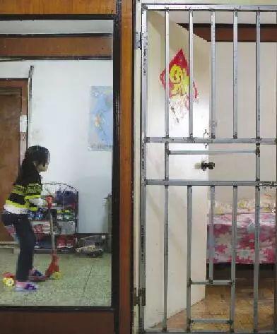 小春莹在屋里玩耍,旁边的铁门曾经用来关患有精神躁狂症的妈妈