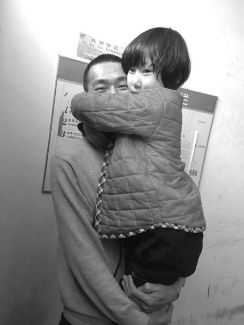 父女俩抱在一起,妞妞眼睛红红的,要求父亲不要再走了。 本报记者 邹俊美 摄