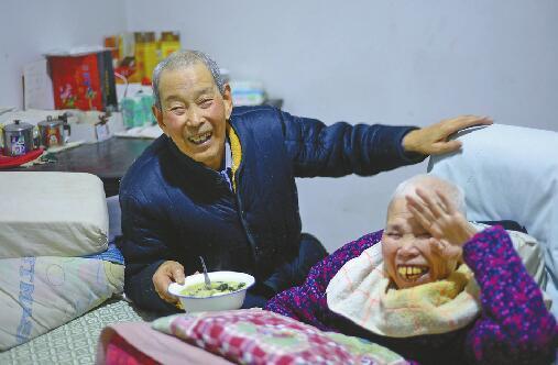 叶老先生正在给老伴喂饭 首席记者王锋 摄