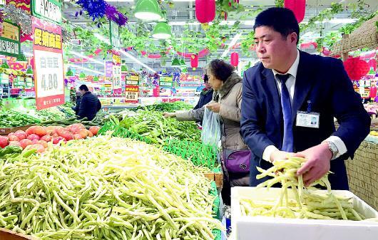 胡作杰在蔬果区补充商品。