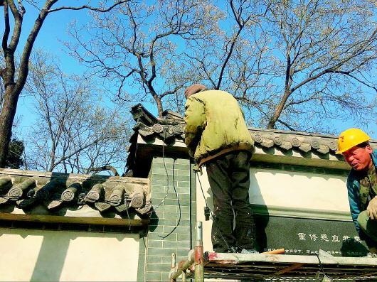 大明湖公园内,工人们正在给建筑安装瓦楞灯。
