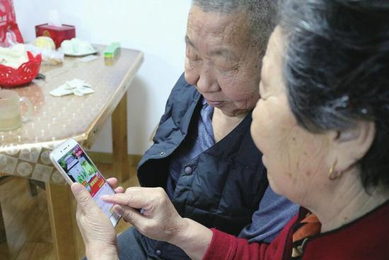 马田英老人和老伴儿正在网上选购商品。(由亚男 摄)