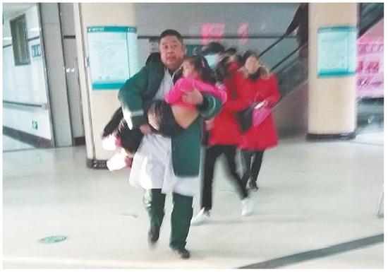 医生抱起患病女孩冲进医院门诊