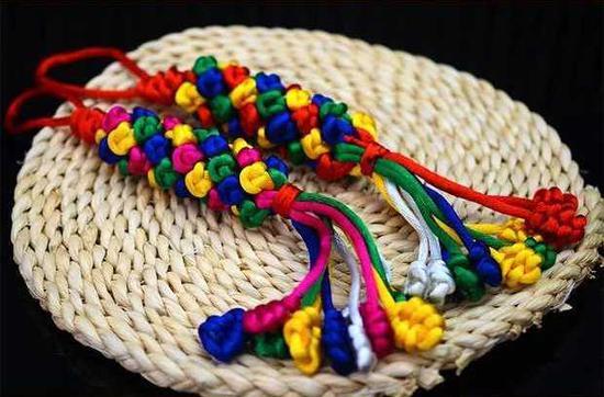 [系五色丝线:中国古代崇拜五色,以五色为吉祥色。因而,节日清晨,各家大人起床后第一件大事便是在孩子手腕、脚腕、脖子上拴五色线。]