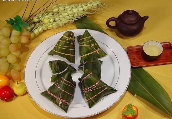 """[端午食粽:粽子,又名""""角黍""""、""""筒粽""""。其由来已久,花样繁多。晋代,被正式定为端午节食品。]"""