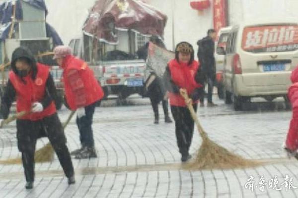 济南持续降雪 义工们冒着雨雪在泉城广场打扫积雪