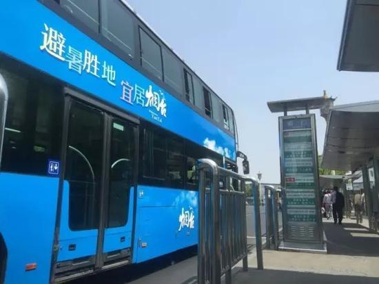 """载有以""""避暑胜地 宜居烟台""""为主题的烟台城市形象宣传广告的北京公交车经过北京前门站牌"""