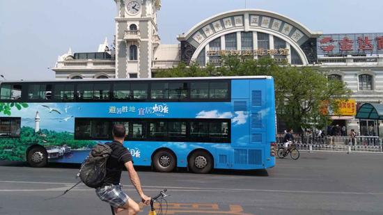 """载有以""""避暑胜地 宜居烟台""""为主题的烟台城市形象宣传广告的北京公交车经过中国铁道博物馆"""