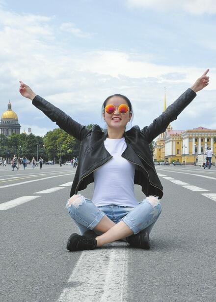 张尧尧坐在圣彼得堡的冬宫广场上。