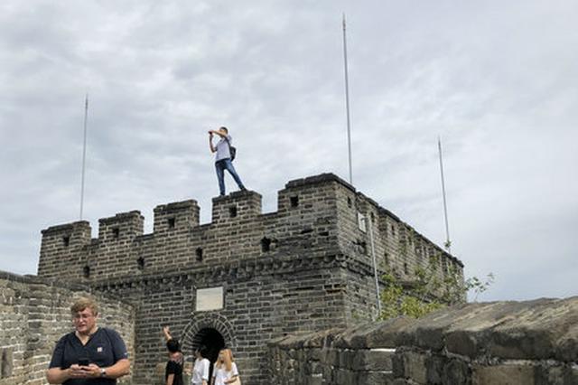 男子攀爬长城烽火台 还跳到城墙垛口上行走(图)