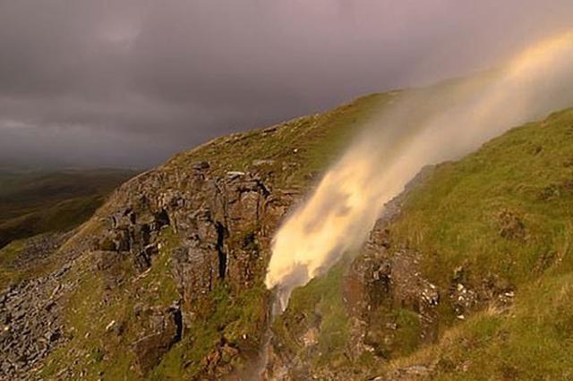 英国暴风致使山顶瀑布倒流 阳光照射挂起彩虹