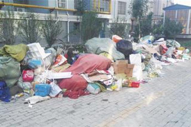 废品堆楼前 居民受影响 物业:再堆放将强行清理