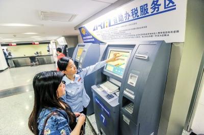 图片说明:在工作人员的帮助下,企业办税人员在自助机上打印发票。