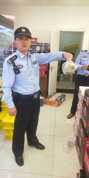 金山一水果店惊现一条蛇 民警抓七寸拎蛇入袋